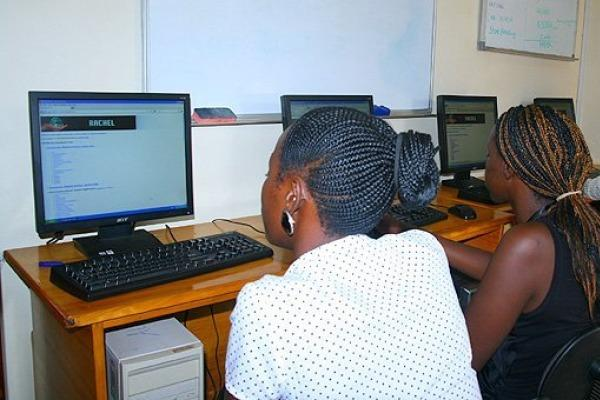 Two young African women work at desktop computers.