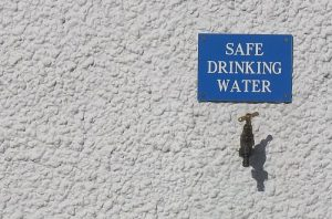 "A tap set into a wall, with sign above reading ""SAFE DRINKING WATER"""
