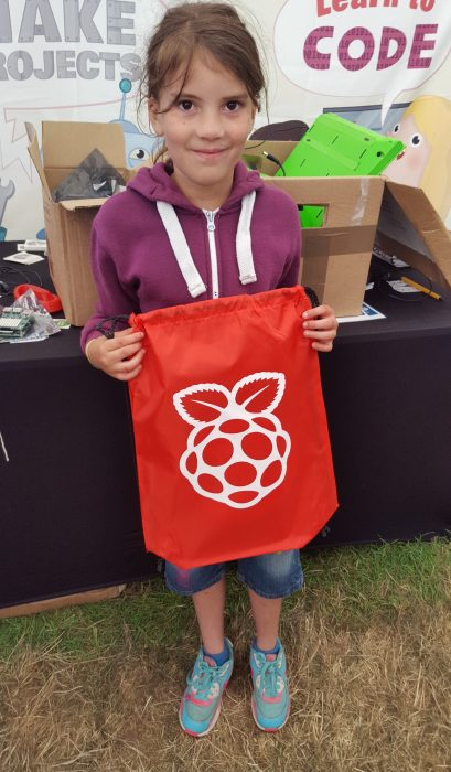 A young girl smiles and holds up a red drawstring bag with a large white Raspberry Pi logo printed on it