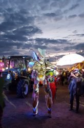 An actor dressed as an exotic alien, with glowing fairy wings and an exoskeleton that incorporates stilts, walks among the crowd at dusk