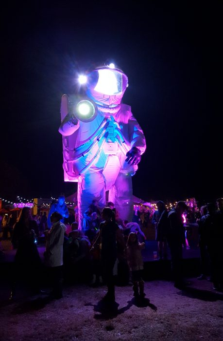 A giant astronaut, glowing purple and blue, towers above the crowd after dark