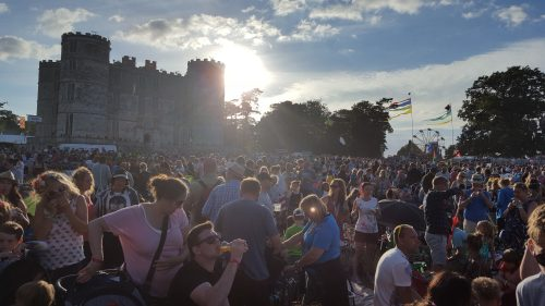A huge crowd in front of Lulworth Castle at Camp Bestival. The sun is setting behind the battlements.