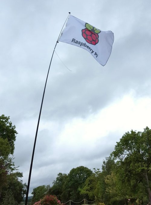 "A white flag with the raspberry and green Raspberry Pi logo and the words ""Raspberry Pi,"" flying in a stiff breeze against a cloudy sky"
