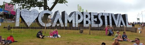 "Festival goers relax on the grass in front of huge silver letters: ""LOVE CAMP BESTIVAL"""