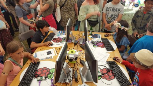 Four children concentrate on activities at Raspberry Pi workstations, with a crowd of older siblings and parents around