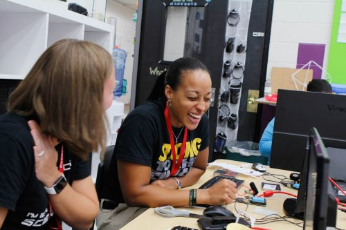 A teacher attending a physical computing sessions laughs as she works through an activity