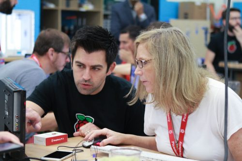 A man and a woman looking at a computer screen while using a Raspberry Pi at Picademy