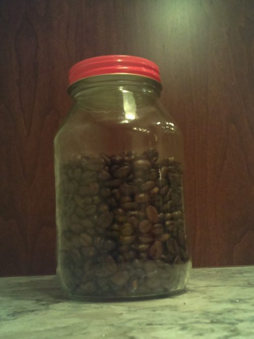 A jar which is almost full of coffee beans