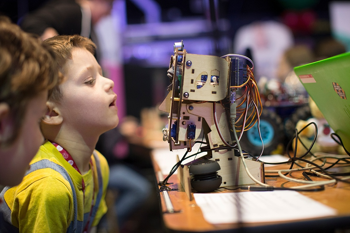Child looking at a handmade robot at the Raspberry Pi fifth birthday weekend