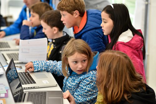 Photo: children concentrate intently on coding activities at a CoderDojo event