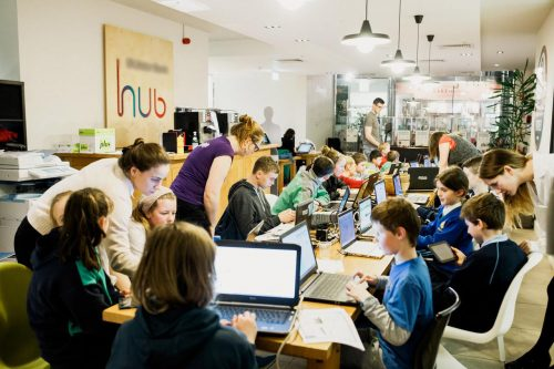 Photo: children and teenagers work on laptops at a CoderDojo, while adults help
