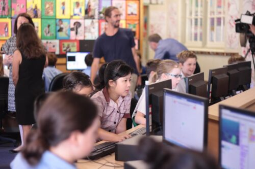 Photo of a Code Club in a classroom: six or seven children focus intently on Scratch programs and other tasks, and adults are helping and supervising in the background