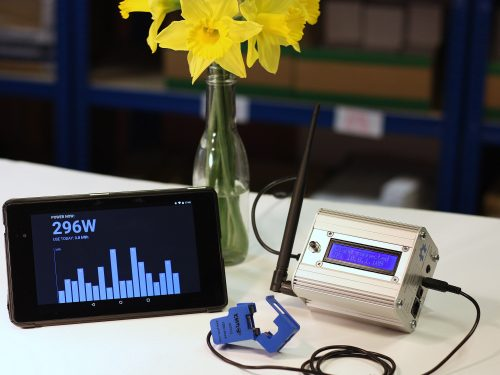 Photo: an emonPi energy monitoring unit in an aluminium case with an aerial and an LCD display, a mobile phone showing daily energy use as a histogram, and a bunch of daffodils in a glass bottle