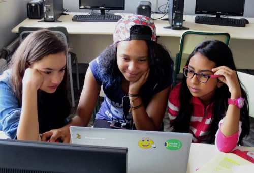 Three girls, all concentrating, one smiling, work together at a computer at Code Club
