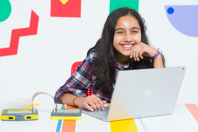 A smiling girl with Pip and a laptop