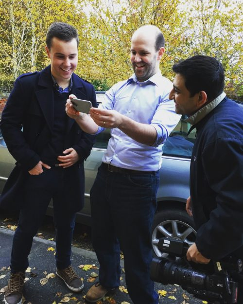 Matthew Timmons-Brown and Eben Upton standing in a car park looking at a smartphone