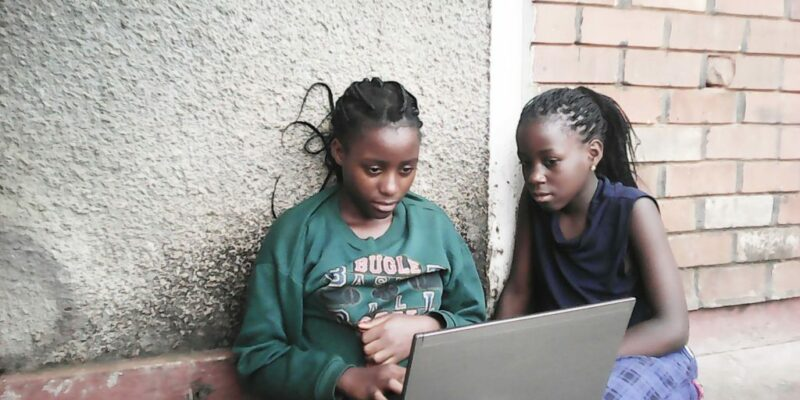 Two black girls sitting against an outside wall while working on a laptop