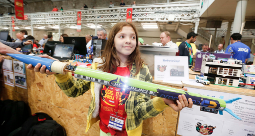 A girl in a CoderDojo Ninja T shirt proudly holds the rocket she has built; it's as long as she is tall