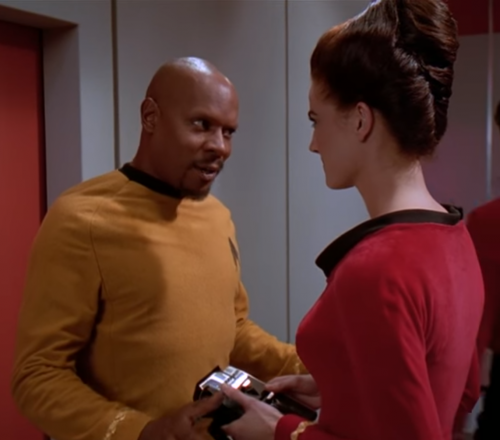 A still from an episode of Star Trek: Deep Space Nine: Jadzia Dax, holding an Original Series-sylte tricorder, speaks with Benjamin Sisko