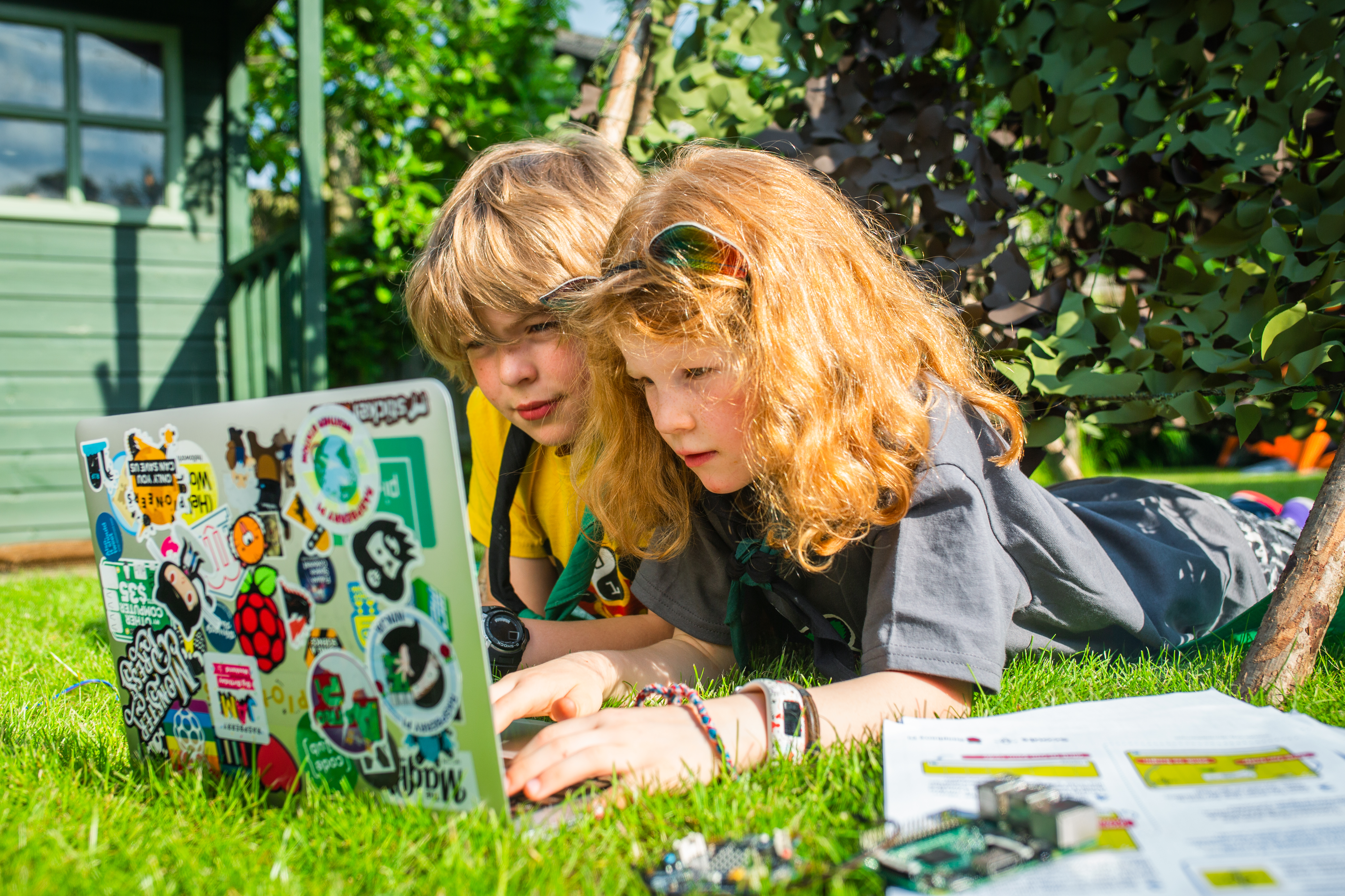 Two young children are propped on their elbows next to one another, using a laptop covered with stickers in a sunny garden. A Raspberry Pi and worksheets are beside them.
