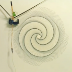 "A blue spirograph-type pattern formed of large overlapping squares, each offset from its neighbour by a few degrees, producing a four-spiral-armed ""galaxy"" shape where lines overlap. The plotter's print head is visible in a corner of the image"