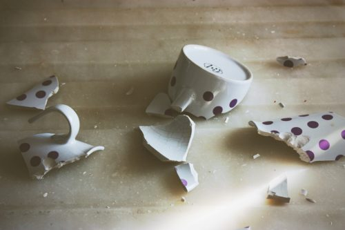 A ceramic mug, broken into several pieces on the floor