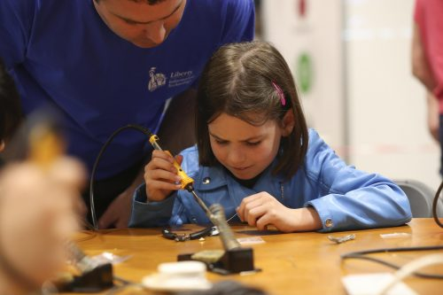 A young girl solders something at a worktop while a man looks over her shoulder.