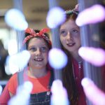 Two smiling girls observe a colourful LED arrangement