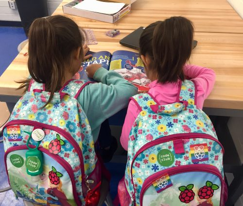 Two girls with backpacks reading about a Raspberry Pi project — Boys & Girls Club