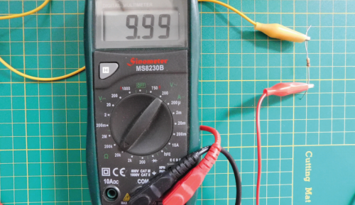 A multimeter showing the figure 9.99 with a resistor connected via crocodile clips