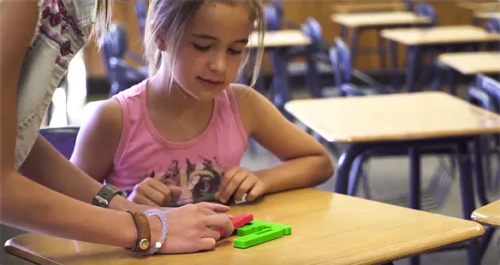 A girl playing with hands-on coding blocks at a desk