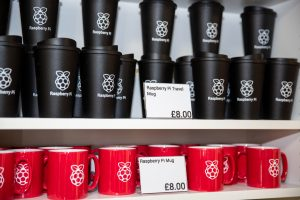 A shelf of Raspberry Pi-branded Travel mugs and ceramic mugs