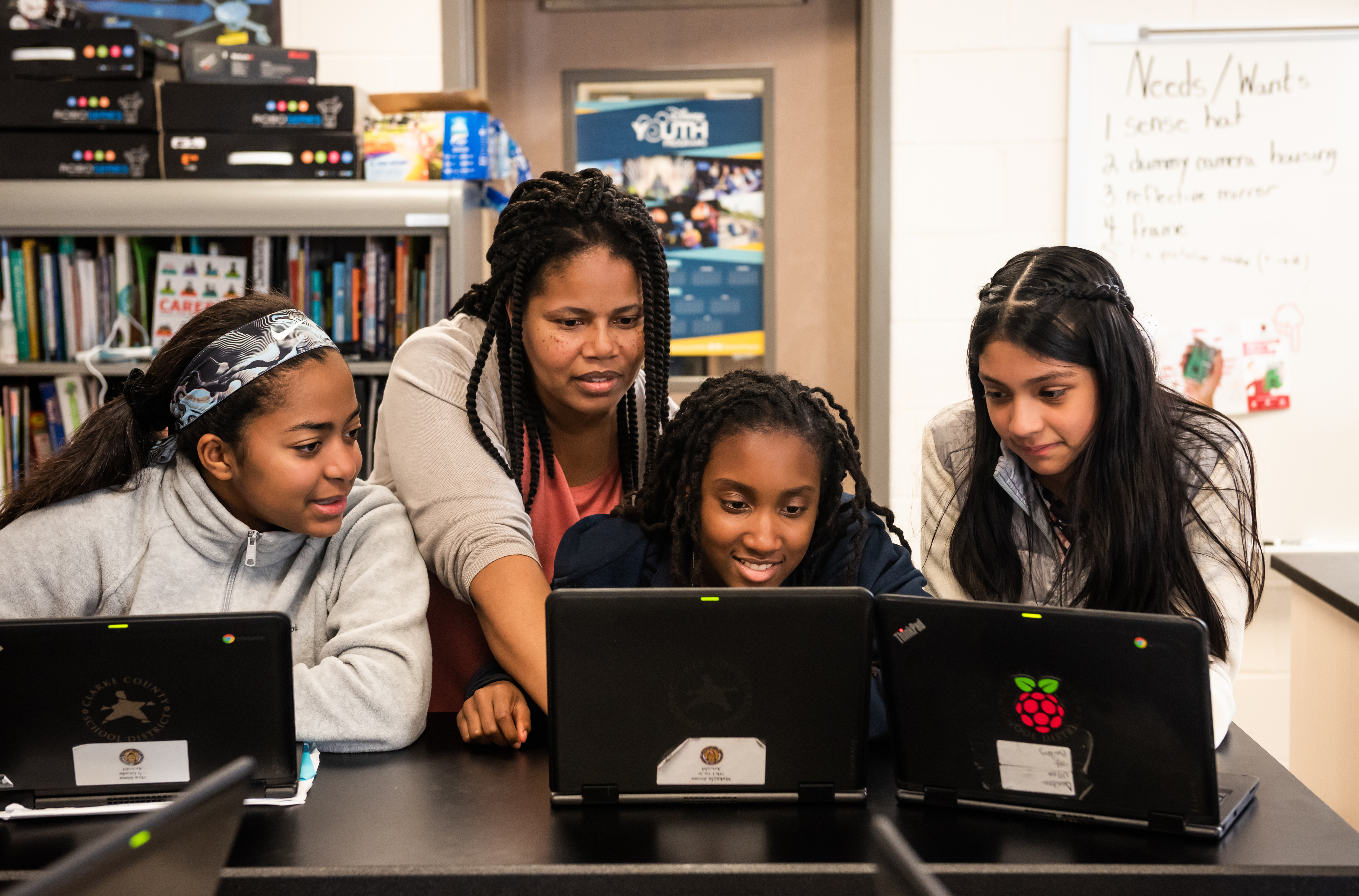 A female computing educator with three female students at laptops in a classroom.