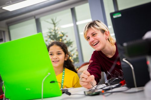 A women and a young girl sit side by side. They are concentrating on a screen connected to a Raspberry Pi and smiling widely