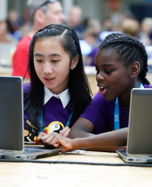 Two girls code at a laptop.