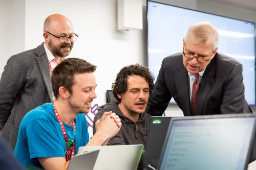 Prince Andrew and three other men watching a computer screen