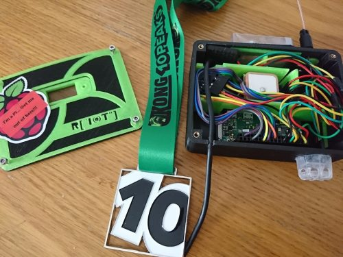The brick, a small plastic box full of coloured jumper leads and other electronics; the lid of the box; and a medal consisting of the number 10 in large plastic characters on a green ribbon