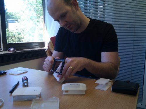 Phone photo of Eben sitting at a desk and hacksawing a white 3D-printed prototype Raspberry Pi case