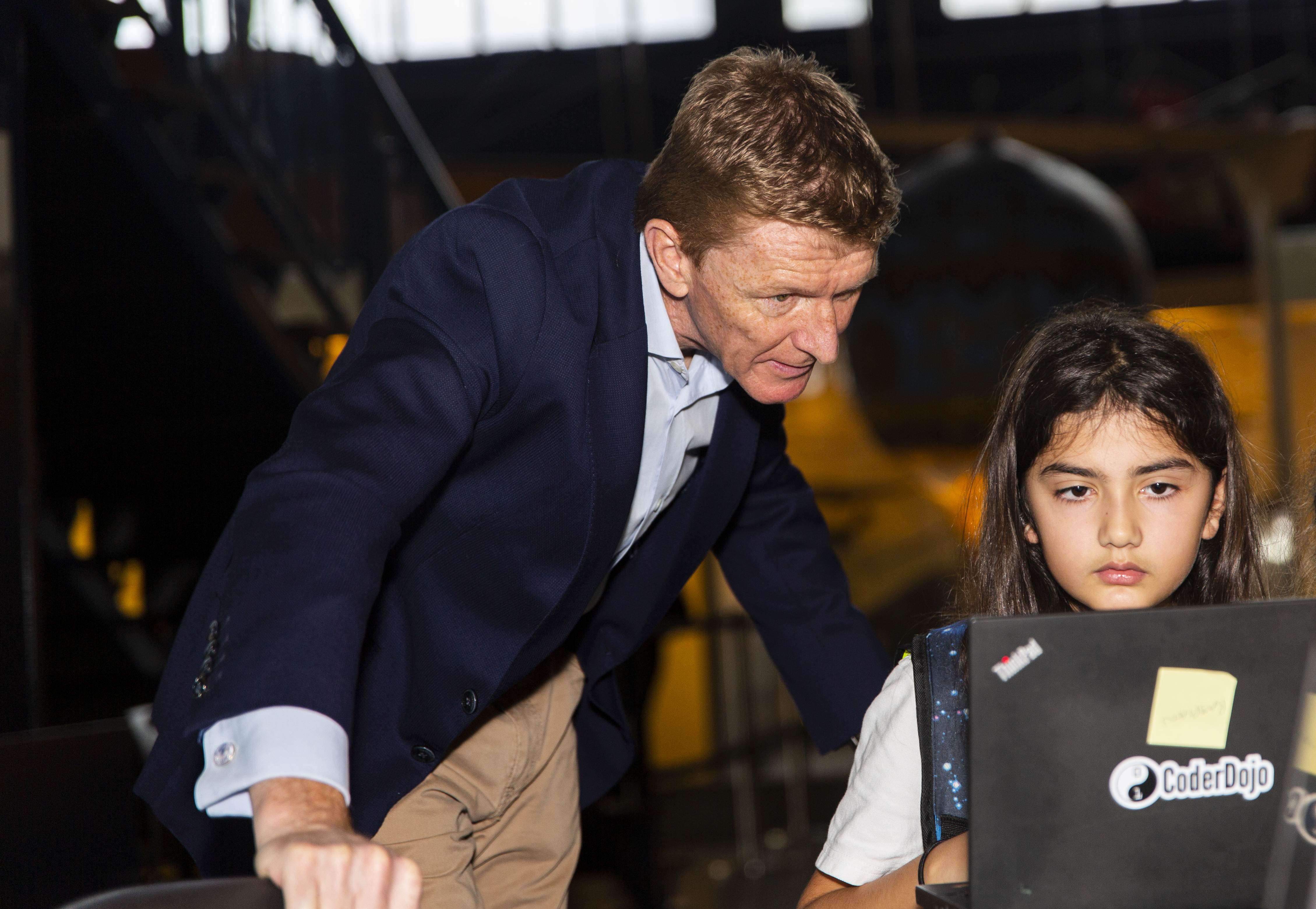Tim Peake observes a girl writing code that will run in space as part of the European Astro Pi Challenge