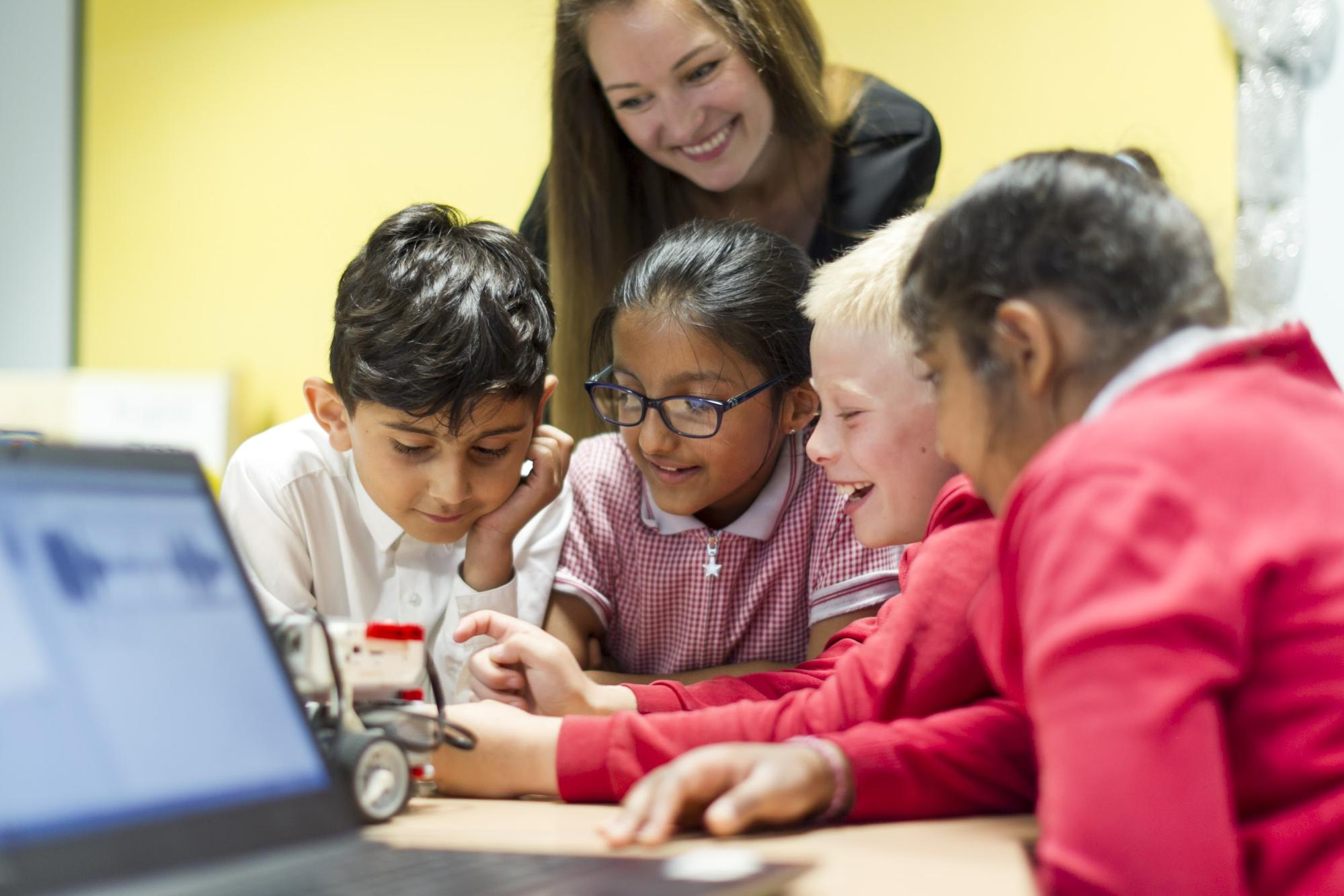 Woman teacher and young students at a computer