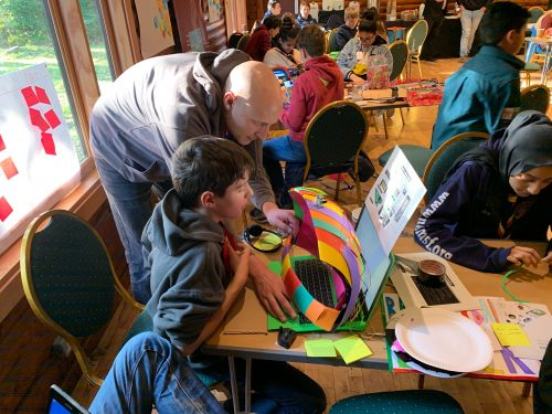 young people engaging in a digital making activity with the help of an educator