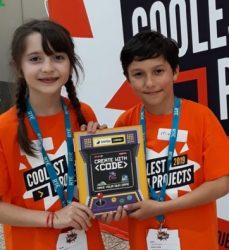 A girl and a boy holding up a book about coding