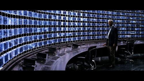 A man standing in front of a wall made of computer screens