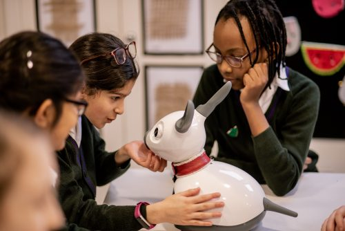 Three school children in uniforms stroke the robot dog's chin