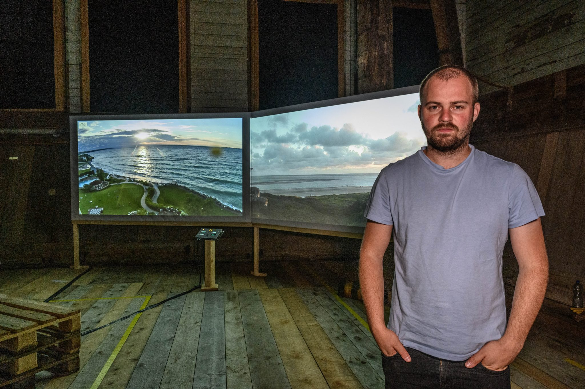 The artist stood infront of the two large display screens