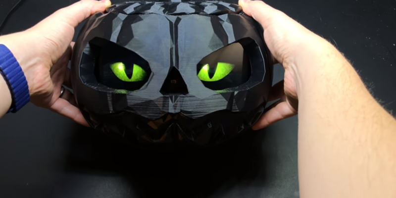 Shiny black 3D printed pumpkin with glowing green cat eyes