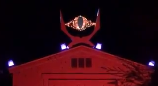 The eye of sauron on top of a barn lit in red lights