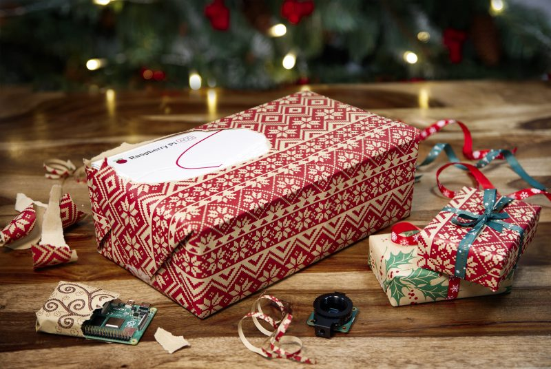 a raspberry pi 400 box peeking out of christmas wrapping paper