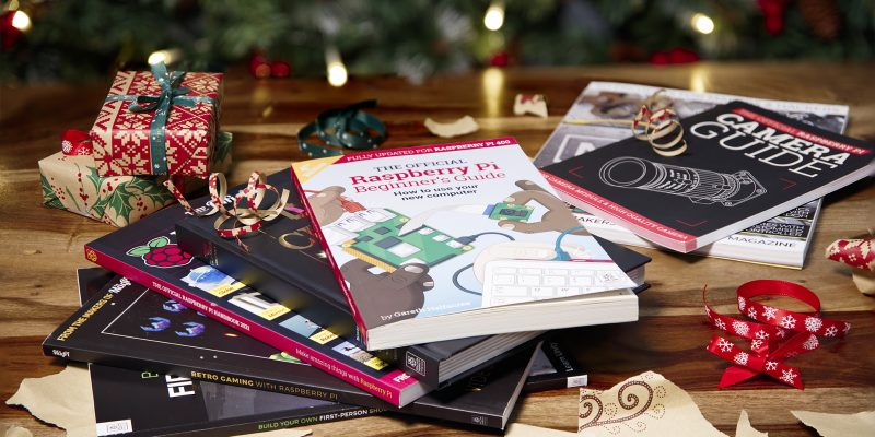 A selection of Raspberry Pi books on a table surrounded by Christmas decorations