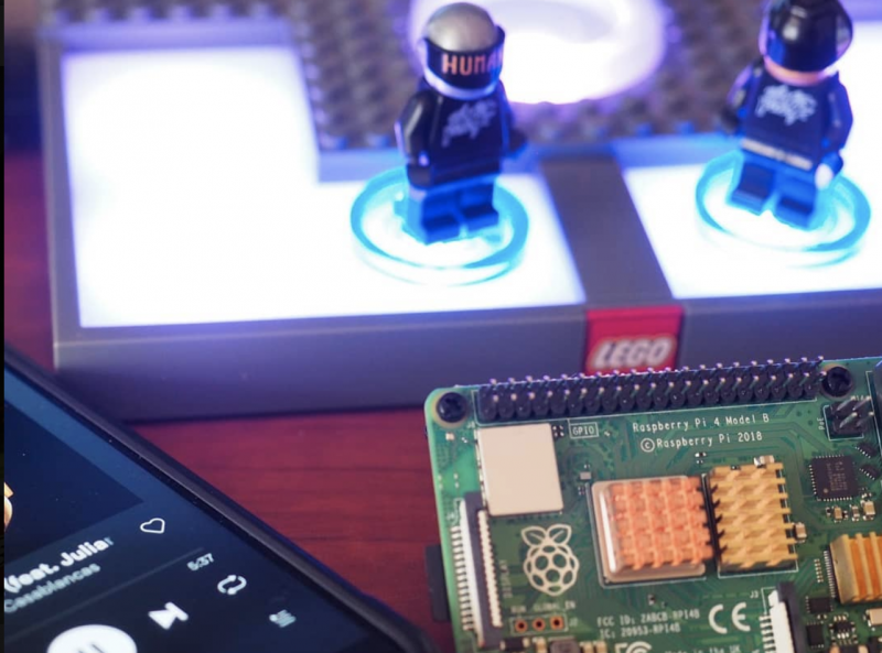 Daft Punk LEGO minifgures stood on an NFC reader next to a Raspberry Pi and a phone showing Daft Punk playing on Spotify